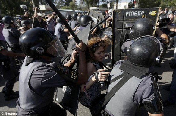 Clash: A woman is pushed by riot policemen during a clash with demonstrators in Sao Paulo, Brazil