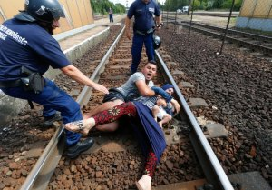 Hungarian policemen stand by the family of migrants as they wanted to run away at the railway station in the town of Bicske, Hungary, September 3, 2015. A camp for refugees and asylum seekers is located in Bicske. REUTERS/Laszlo Balogh - RTX1QVYM