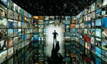 Man in a room filled by screens